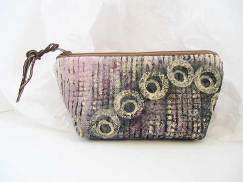 Small zipper pouch of painted canvas.